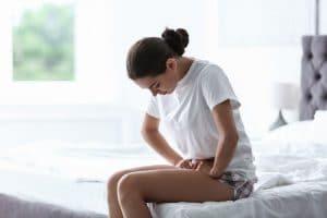 אישה מקופלת מכאב